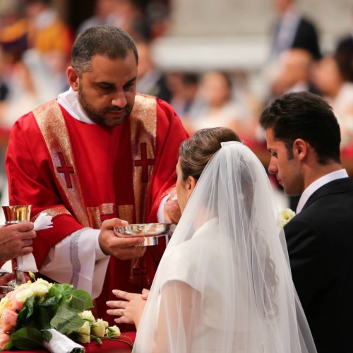 A couple newly married by Pope Francis receives Communion in St. Peter's Basilica on Sept. 14.
