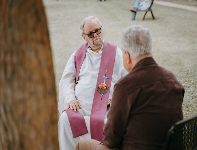 "Father Giancarlo Ghezzi, associate pastor of St. Mary of the Immaculate Conception Parish in Monroe, hears a man's confession during the Monroe Vicariate's ""Priests in the Park"" event June 17."
