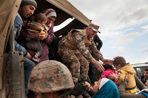 Jordanian troops and U.N. members help bring refugees to the Zaatari refugee camp.