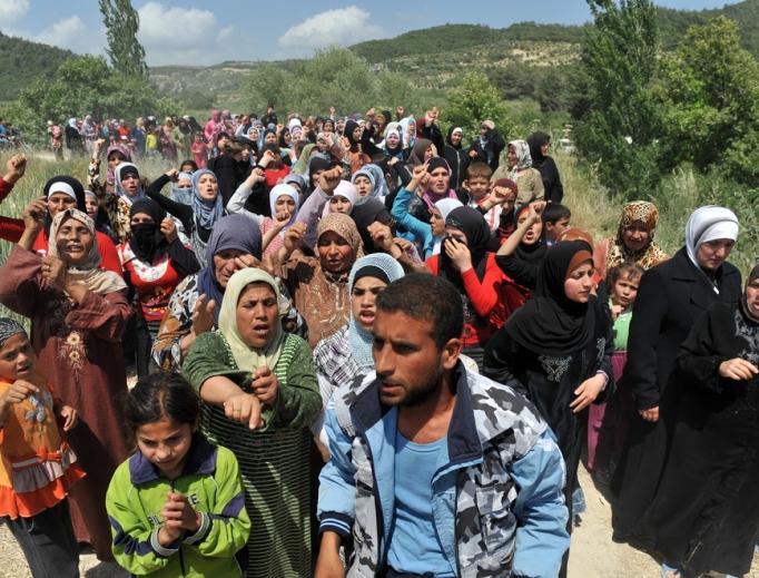 Syrian refugees gather on the Syria/Turkey border.