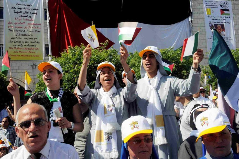Nuns sing while holding Vatican and Palestinian flags as Benedict celebrates Mass in Manger Square in Bethlehem.