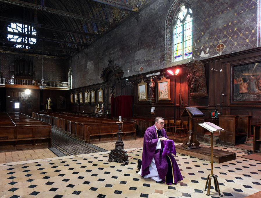 French priest Olivier Monnier broadcasts a Mass with a video chat application running on his smart phone fixed on a wooden candlestick facing the altar on April 3, 2020 at the empty Saint-Jacques church in Illiers-Combray, France.
