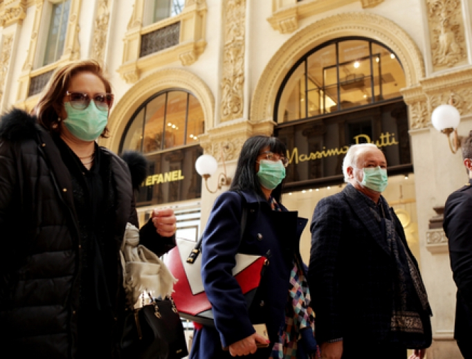 As coronavirus hits Italy, tourists wear protective masks at the Wiktor Emanuel II Gallery in Milan Feb. 22.