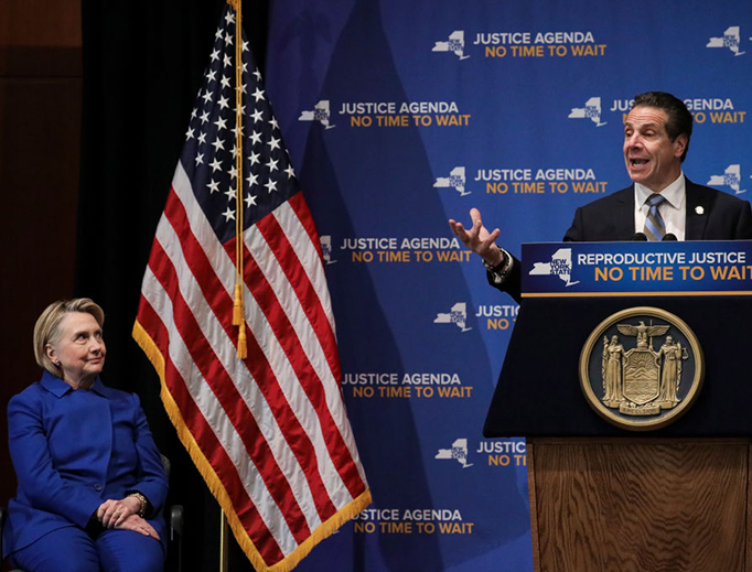 Former Secretary of State Hillary Clinton looks on as New York Governor Andrew Cuomo speaks about abortion at Barnard College, Jan. 7, 2019, in New York City. The two Democrats shared the stage to promote the Reproductive Health Act in New York.