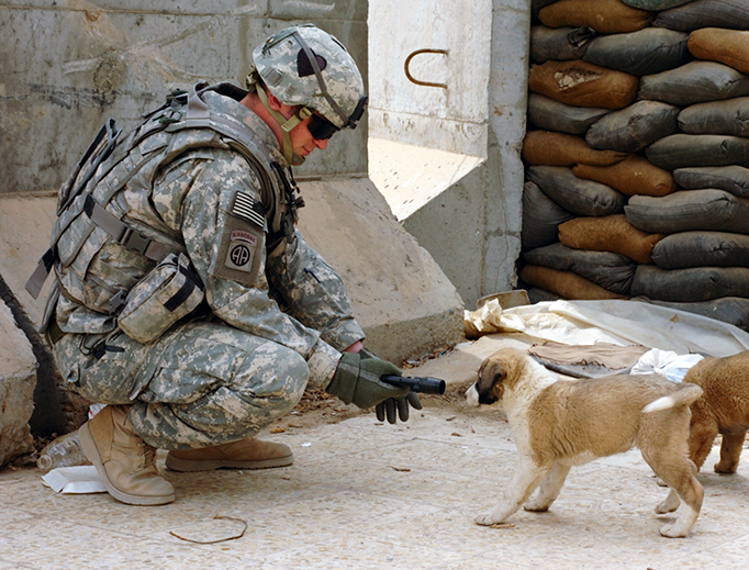 Sgt. Steven Olesen, a busy man, plays with a puppy in this Feb. 24, 2008 file photo.