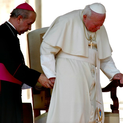Then-Archbishop Stanislaw Dziwisz helps Pope John Paul II to his chair as the Holy Father arrives for his weekly general audience on Oct. 2, 2002.