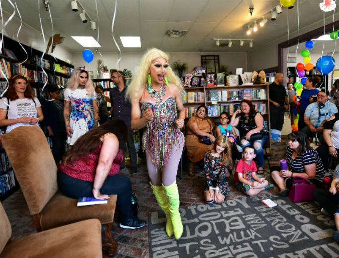 Performance artist Athena Kills greets young adults and children as he and fellow cross-dressing performance artist Scalene Onixxx arrive for 'Drag Queen Story Hour' at Cellar Door Books in Riverside, California, June 22.