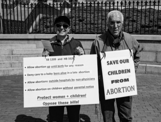 A couple protested abortion outside of Massachusett's State House in Boston, April 29, 2019.