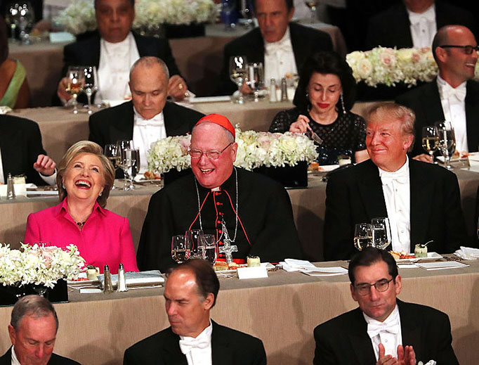 Cardinal Timothy Dolan sits between Hillary Clinton and Donald Trump at the annual Alfred E. Smith Memorial Foundation Dinner at the Waldorf Astoria on October 20, 2016 in New York City.
