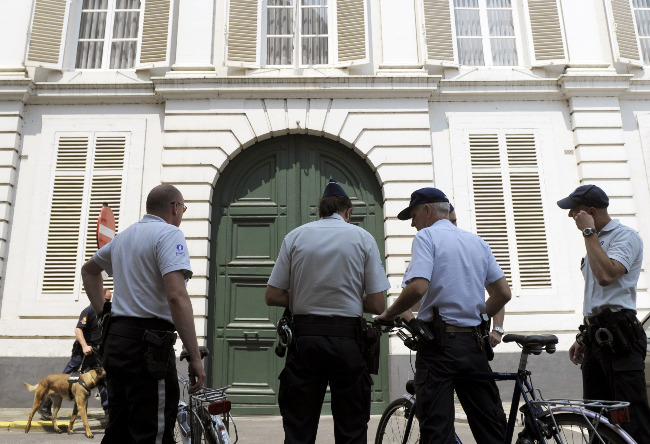 Police officers stand outside the residence of the archbishop of Mechelen-Brussels in Mechelen, Belgium, June 24. Belgian investigators searched Church headquarters in Belgium, the archbishop's residence as well as the home of Cardinal Godfried Danneels as part of an investigation into alleged priestly sexual abuse.