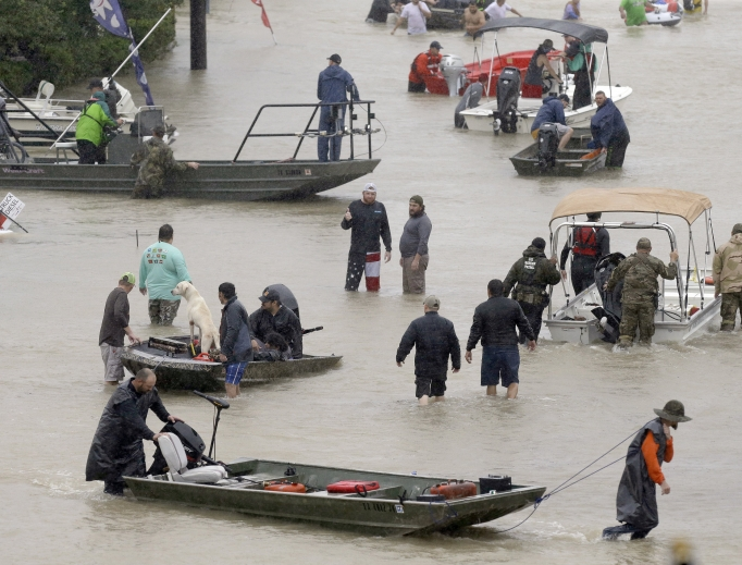 Above, people and rescue boats line a street at the east Sam Houston Tollway as evacuations continue from flooding in Houston Aug. 28. Below, a rescuer moves Paulina Tamirano, 92, from a boat to a truck bed as people evacuate from the Savannah Estates neighborhood as Addicks Reservoir nears capacity Aug. 29 in Houston. Houston Police SWAT officer Daryl Hudeck carries Catherine Pham and her 13-month-old son, Aiden, after rescuing them from their home surrounded by floodwaters Aug. 27 in Houston. An image of Our Lady of Guadalupe sits on Hickory Lane in Crosby, Texas, Sept. 1. Staff Sgt. Lawrence Lind, left, hoists a child into a Black Hawk helicopter while Sgt. Ray Smith, right, helps the boy who was rescued in Port Arthur, Texas, Aug. 30.