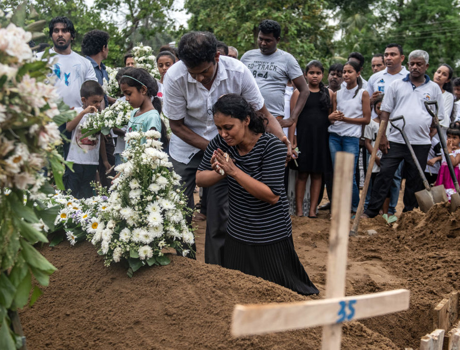 A woman grieves at the grave after a funeral for a person killed in the Easter Sunday attack on St Sebastian's Church, on April 25, 2019, in Negombo, Sri Lanka.