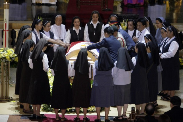 Nuns circle the casket of former Philippine President Corazon Aquino during services at the cathedral in Manila Aug. 3.