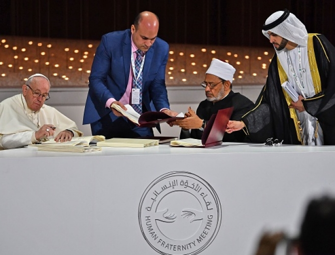 Pope Francis and Egypt's Azhar Grand Imam Sheikh Ahmed al-Tayeb (second from right) sign documents during the Human Fraternity Meeting at the Founders Memorial in Abu Dhabi Feb. 4.