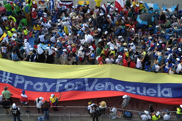 Pilgrims hold a giant flag reading 'Pray for Venezuela' as they wait Jan. 24 for the arrival of Pope Francis for his welcoming ceremony at Campo Santa Maria La Antigua in Panama City during World Youth Day.