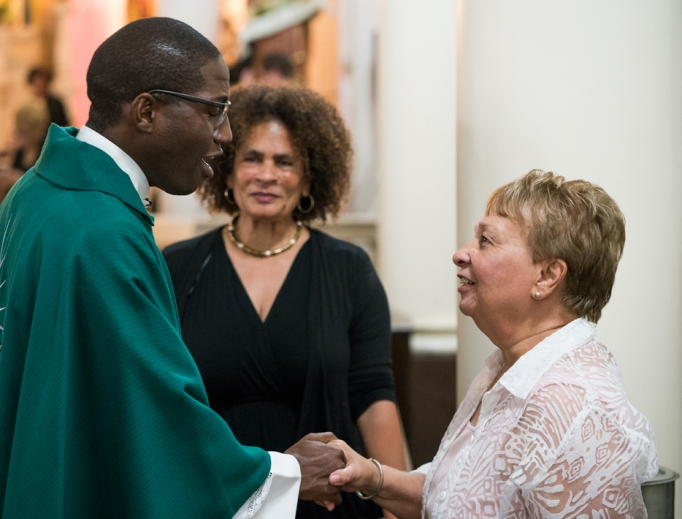 Father Emmanuel Mulenga, a Missionary Oblate of Mary Immaculate, greets a parishioner at St. Augustine Catholic Church, where Father Mulenga is pastor, in New Orleans.