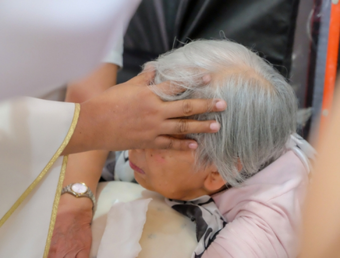 Priest anoints a woman's head with oil.