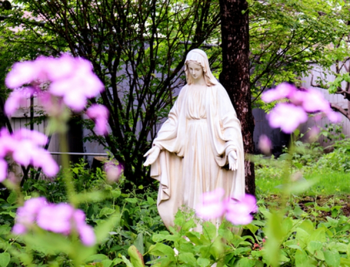 Blessed Virgin amid the flowers in a Mary Garden.
