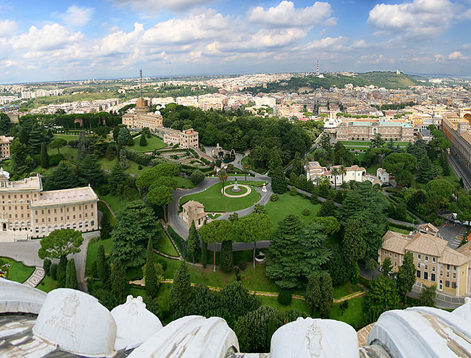 A Bird's Eye View of the First Vatican Radio Tower. When Vatican Radio first began operations in 1931, it broadcast from a tower within the Vatican Gardens, behind St. Peter's Basilica. Here, in the background, the tower can be seen from the Dome of St. Peter's Basilica. On the left (forefront) is the Palace of the Governatorato, the offices of the Vatican City State. At the right are the Vatican Museums. And in the distance, near the wall of Vatican City and behind the Mater Ecclesiae Monastery where Pope-emeritus Benedict XVI now resides, is the radio tower.