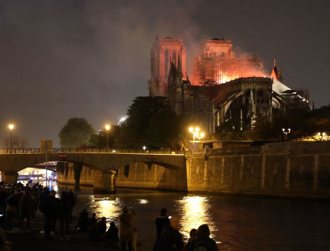 People stand on the banks of the River Seine as flames engulf the Notre-Dame Cathedral in Paris on April 15, 2019.