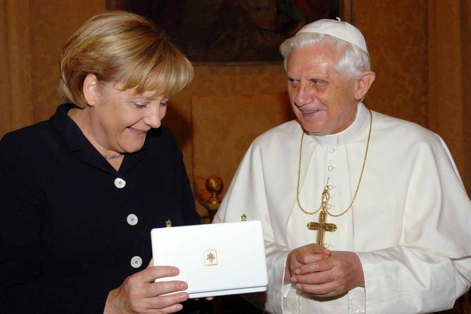 German Chancellor Angela Merkel receives a gift from Pope Benedict XVI during a meeting in August 2006.