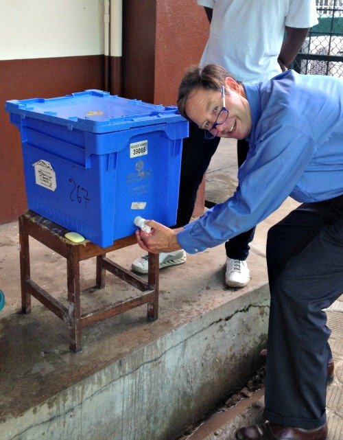 Dr./Deacon Timothy Flanigan sanitizes his hands at a Liberia medical clinic.