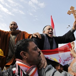 COMMON CAUSE. A Muslim man holding the Koran and a Coptic Christian man holding a cross were carried through demonstrators in Tahrir Square in Cairo Feb. 6.