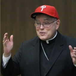Archbishop Charles Chaput dons a Phillies hat at the July 19 press conference announcing his new appointment.