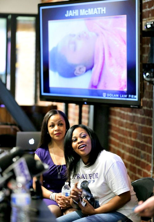 Nailah Winkfield (r), mother of Jahi McMath, looks up at a video of her daughter being played during a news conference at a law office in San Francisco.