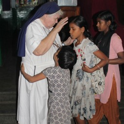 Girls get a good night blessing from Loreto Sister Cyril Mooney at the Rainbow Home in Kolkata, India, Feb. 11. Rainbow Home is a care and schooling program started by Sister Mooney for the orphans and street girls.