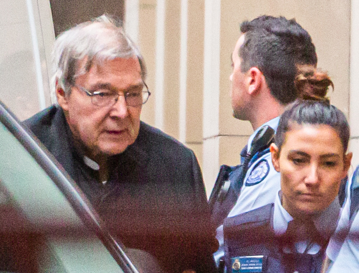 Cardinal George Pell is escorted into the Supreme Court of Victoria in Melbourne for his appeal hearing on Thursday