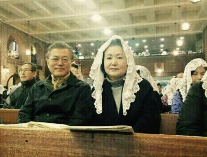 """Above, President Moon Jae-in and the first lady, Kim Jung-sook, a classical singer, attend Hongje-dong Catholic Church in Seoul. President Moon won popular election last May as the solution to a political crisis that saw the impeachment of his predecessor. Below, Father Paul Yoo, the pastor, and four women religious who serve Hongje-dong Catholic Church in Seoul celebrate the blessing of Korea's """"Blue House,"""" where President Moon and his wife live."""