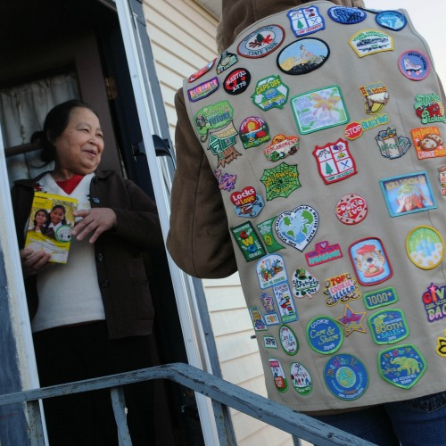 A Girl Scout, wearing her vest covered in badges, sells a box of cookies to a neighbor in Minneapolis.