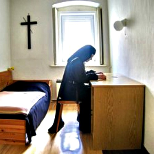 A Carmelite nun meditates on the Bible in her room.