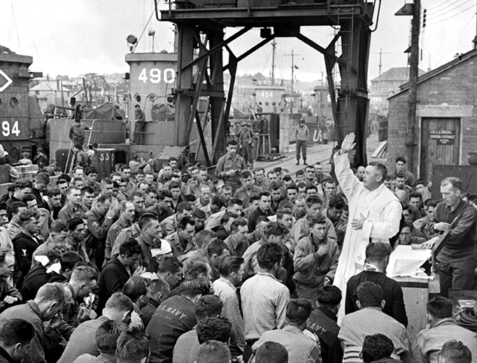 Father (Major) Edward J. Waters, a U.S. Army chaplain from Oswego, New York, blesses U.S. military personnel in Weymouth, England, on June 6, 1944.