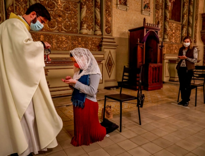 Father Lucas Mendes, wearing a protective face mask, gives Holy Communion to a worshipper during Mass at the Nossa Senhora das Dores Church in Porto Alegre, in southern Brazil, on May 29. American infectious-disease experts say that going to Mass is one of the safest activities amid the pandemic.