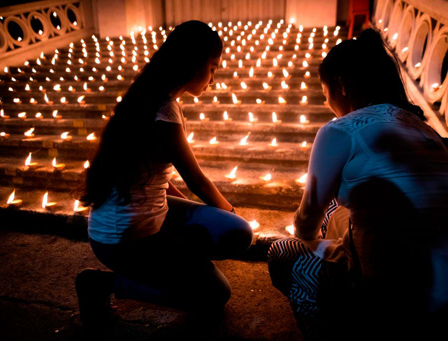 Mourners light candles during a vigil in memory of the bomb blast victims in Colombo on April 28, 2019, a week after a series of bomb blasts targeting churches and luxury hotels on Easter Sunday in Sri Lanka.