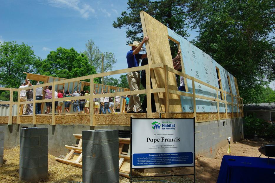 Many volunteers raise the walls for 'The Pope Francis House' being built by Habitat for Humanity in Asheville, N.C.