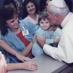 Pope John Paul II kisses Angelina Tsukas-Spiera, 1, at St. Joseph's Hospital in Phoenix in 1987.