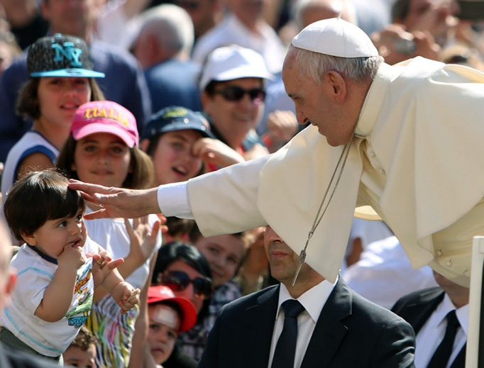 Pope Francis reaches out to embrace a little child in the crowd in St. Peter's Square.