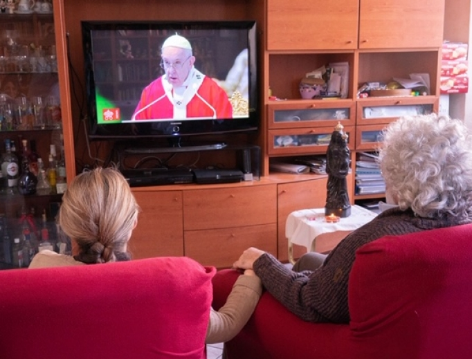 A family follows the Pope's Palm Sunday broadcast from home, April 2020.