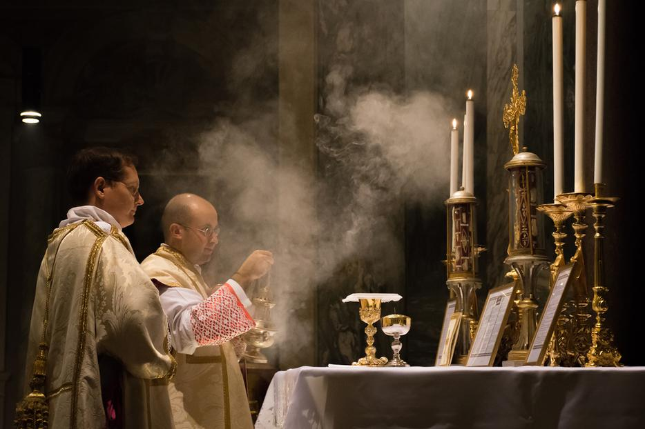 A Catholic priest celebrates the traditional Latin Mass with a deacon and subdeacon, incensing the altar in the Church of St. Pancratius, Rome.