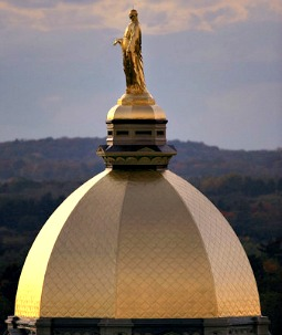 A statue of the Blessed Mother stands atop the golden dome of the Main Building.