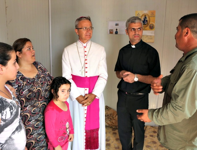 From top: Bishop Francesco Cavina of Carpi, Italy, meets with a Syriac Orthodox family who have been in the Dawudiya Refugee Camp near Duhok for 14 months. Haney, an 86-year-old Syriac Catholic, was kidnapped along with her son by Islamic State forces. After being released, they fled to Duhok then to Dawudiya, in Iraqi Kurdistan. Sadalla and his family fled from his town outside Mosul to escape from ISIS. They have taken refuge at the catechesis center in Mangesh for more than two years. 'God willing, we'll be able to go back to our home town soon. Until ISIS invaded, we lived with Muslims and Yazidis without any problems.' Illuminated crosses adorn almost every caravan at the Asti 2 refugee camp in Ankawa, Erbil, Iraq, the largest Christian camp in Kurdistan.