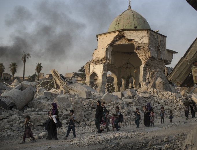 Fleeing Iraqi civilians walk past the heavily damaged al-Nuri mosque as Iraqi forces continue their advance against Islamic State militants in the Old City of Mosul, Iraq, July 4.