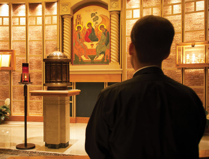 A Theological College seminarian at prayer before the tabernacle.