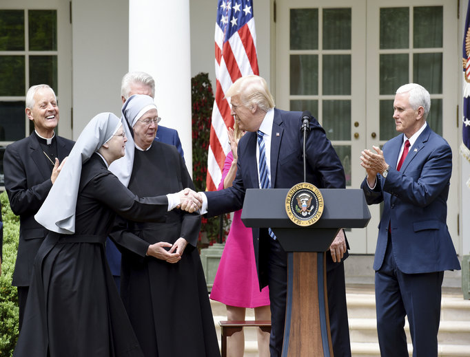 President Donald Trump greets on stage the Little Sisters of the Poor, flanked by Cardinal Donald Wuerl of Washington and Vice President Mike Pence, before signing the executive order on promoting free speech and religious liberty during a National Day of Prayer event in the Rose Garden of the White House in Washington, D.C., on May 4.