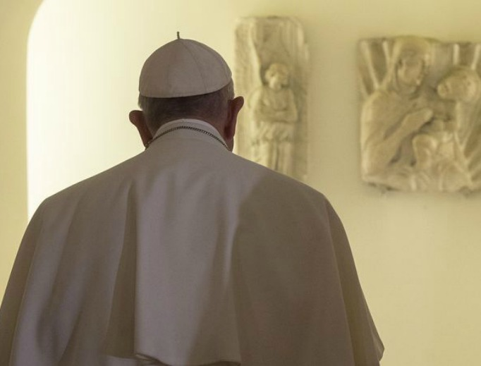 Pope Francis prays before the tombs of past popes in the grotto of St. Peter's Basilica, Nov. 2, 2015.
