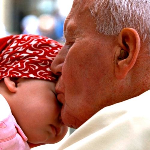 Pope John Paul II kisses a child as he leaves St. Peter's Square at the end of his weekly general audience at the Vatican on April 30, 2003.