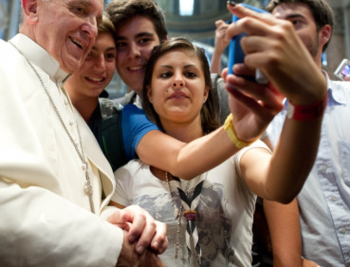 Pope Francis and youth take a selfie.